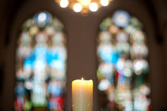 Church interior with candle. Church interior with burning candle in foreground and beautiful colorful stained glass windows in background Stock Image