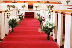 Church interior decorated for wedding. Red carpet and flower decorating church for wedding ceremony Stock Photography