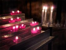 Church Interior Lit Prayer Candles. Fire. Flame. Prayer candles are lit in church interior. Location is parish in France royalty free stock image