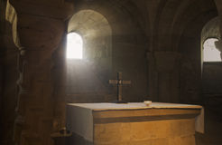 Church interior. A modern altar in front of a crypt window in an ancient cathedral. Beautiful sunlight shining in on the cross stock photos