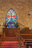 Church Interior with Stained Glass WIndow. Interior of the little, historic, Gothic revival church of La Villita, San Antonio, Texas, with its pews leading up to Royalty Free Stock Photos