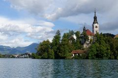 Church on an island on Bled lake with mountains and resort on the background Royalty Free Stock Photos