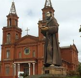 Church and its corresponding saint. Image of Saint Francis of Assisi in front of the church royalty free stock image