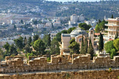 The Church  in Jerusalem. The morning sun illuminates the dome. The Church  in Jerusalem. Battlements of Jerusalem surrounded by majestic building.  On the wall Stock Photos