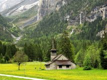 Church at Kandersteg, Switzerland, backed by mountains and waterfalls. Church in an alpine meadow at Kandersteg, Switzerland, backed by rocky mountains and stock photo