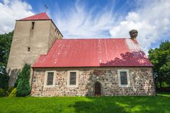 Church in Kartno. Stork nest on a roof of church of Elevation of Holy Cross in Kartno, small village in Poland Stock Photos