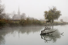 Church by the lake in fog Stock Photo