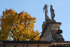 Church, with large tree by yellow leaves, of St. Nicholas in the village and castle of Strassoldo Friuli (Italy) Royalty Free Stock Photography