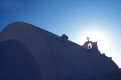 Church and light. Bell and cross against the sun on a Greek church Stock Photography