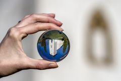 Church in Martincek, Slovakia. Crystal lensball photo. Reflection of church of St. Martin in village Martincek, Slovakia. Crystal lenball in hand royalty free stock photography