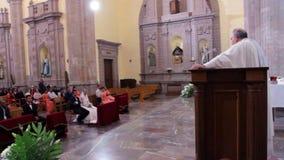 A church minister celebrating a wedding in a Catholic church. QUERETARO, MX-CIRCA MAY 2016 (FULL SHOT): A church minister celebrating a wedding in a Catholic stock footage