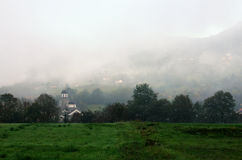 Church in mist near Bajina Basta, Serbia. Beautiful autumn picture with meadow, church and hill in the mist Royalty Free Stock Images