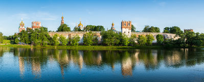 Church and monastery in forest with lake in sunshine panorama. Classic Orthodox church in the forest in sunshine panorama Royalty Free Stock Image
