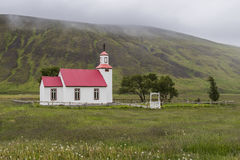 Church with Mountain on Iceland. Church with red roof on Iceland with some small trees and mountains in the background Stock Photo