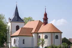 Church named Nanebevzeti panny Marie in Vraclav village, sacral historic heritage with tower nad red roof on the hill, blue sky. And sunlight Royalty Free Stock Photo