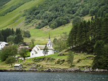 Church in the Norwgian Fjords. Wooden church located on the shore of a Norwegian fjord, around green meadows and forests Royalty Free Stock Photography