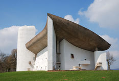 The Church of Notre-Dame du Haut. Modest church by Le Corbusier is congruous to the landscape. Concrete building with curvilinear roof is photographed from below Stock Images