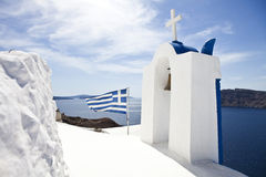Church in Oia village on Santorini. An a Greek Flag Royalty Free Stock Photography