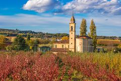 Church in autumn orchards. Church among orchards in the fall in the hills Royalty Free Stock Images