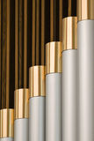 Church Organ Pipes. Brass trimmings of the church organ pipes gleam in the day light Stock Photos