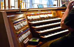 Church organs player at work. Poznan, Poland: church organs keyboards and controls, the player ready to perform royalty free stock images