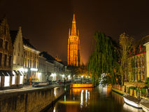 Church of Our Lady in Bruges at night. Church of Our Lady and bridge over water canal at night, Bruges, Belgium Royalty Free Stock Photos