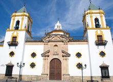 Church of Our Lady del Socorro. Located in the Spanish village of Ronda is a White and yellow church on a sunny day Stock Photos