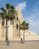 Church of Our Lady of the regla. Located in the Spanish village of Chipiona is a yellow church on a sunny day with palm tree Stock Photos