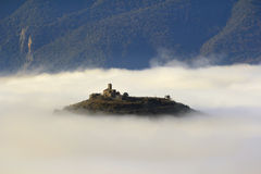 A church over a hill in the middle of a sea of ??fog Stock Image