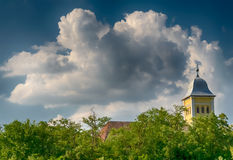 Church over the trees, cloudy blue sky Royalty Free Stock Images