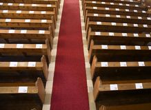 Church pews. Church benches ready for service and a red carpet in the middle. Canon 5D, 24-105, raw royalty free stock image