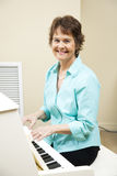 Church Pianist. Pretty mature woman enjoys playing piano at her church Stock Photo