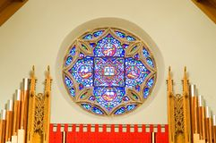 Church pipe organ and window. A view of the pipes of a church organ and beautiful stained glass window in the chancel of a modern Protestant church Royalty Free Stock Image