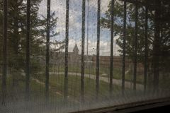 Church in prison yard through bars Stock Images
