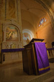 Church Pulpit, Christian Religion. Wood pedestal or church pulpit, a common sight in a church for the Christian religion. A purple robe adds color and is a Royalty Free Stock Photos