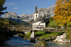 Church in Ramsau. With mountain brook and wooden bridge Stock Photo