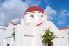 Church with red dome in Mykonos, Greece. Chapel building architecture on sunny outdoor. White church on cloudy blue sky. Summer vacation on mediterranean Stock Photo
