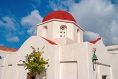 Church with red dome in Mykonos, Greece. Chapel building architecture on sunny outdoor. White church on cloudy blue sky royalty free stock image