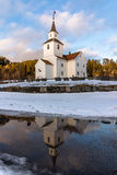 Church reflected in water, winter, snow and blue sky in Iveland Norway, vertical. Church in march, winter landscape with snow and blue sky in Iveland in the Royalty Free Stock Images
