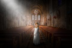 Church, Religion, Christian, Christianity, Religious, Girl. A young girl wearing a white dress stands in a Christian church with a light from heaven and god royalty free stock image
