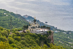 Church of the Resurrection of Christ. Orthodox church over the village of Foros, built in 1892 on a steep cliff - the Red Rock. The height of the building stock photo