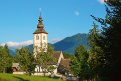 Church in Ribcev Laz, Slovenia located on the shore of lake Bohinj with a daytime moon over it. Church of St John the Baptist in Ribcev Laz, Slovenia located on Stock Photography