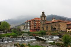 Church with river and waterfall in foreground of Balmaseda Royalty Free Stock Image