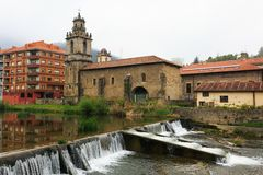 Church with river and waterfall in foreground of Balmaseda Stock Photos