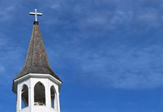 Church roof with metal cross on top and white bell tower with fluffy clouds royalty free stock photos