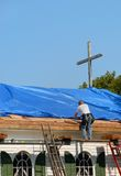 Church Roof Repair. Man standing on a ladder repairing roof, with blue tarp, of church Royalty Free Stock Images