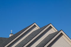 Church Roof. Three gabled church roof with cross against a clear blue sky stock photos
