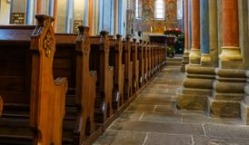 Church room of a medieval church with rows of wooden benches and coloured columns leading to the chancel with a magnificent. Ceiling painting royalty free stock image