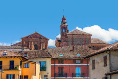Church's bell tower and colorful houses in La Morra. Stock Photography