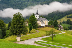 Church of saint Nikolaja in Sorica, Slovenia. With low clouds in mountains stock photo